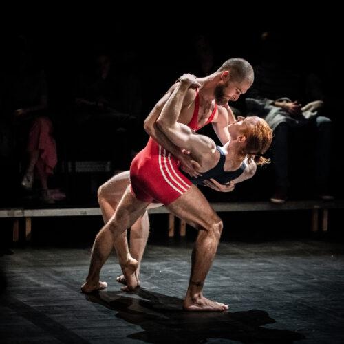 Dwóch mężczyzn w strojach zapaśników w pozie tanecznej: jeden przechyla drugiego do tyłu trzymając go za plecy, drugi chwyta go za ramiona, patrzą na siebie.