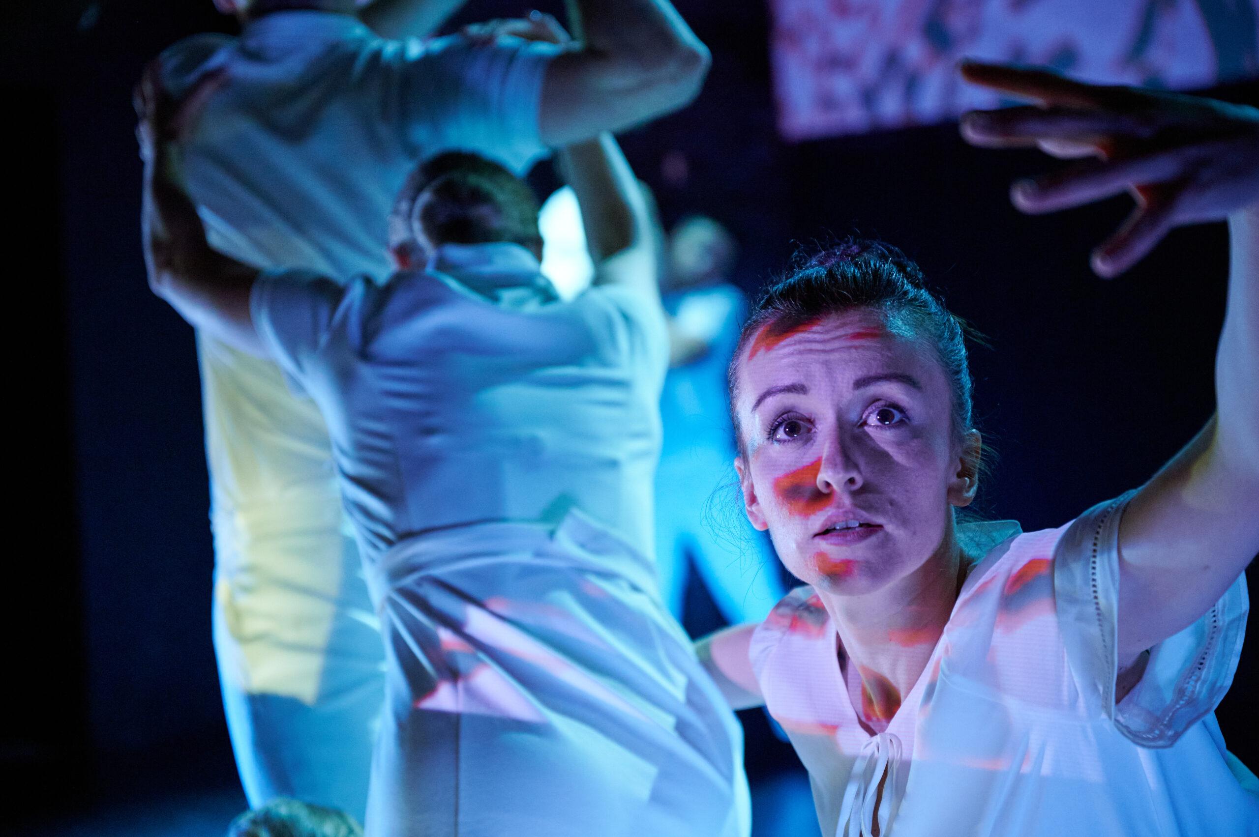 Na pierwszym planie twarz dziewczyny z szeroko otwartymi oczami, jedną rękę ma wyciągniętą przed siebie, drugim ramieniem obejmuje jakąś ubraną na biało, odwróconą tyłem postać kobiety. W tle jeszcze dwie męskie sylwetki.